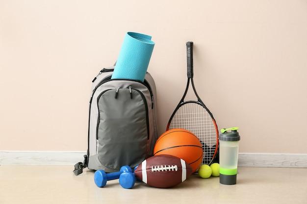 Set van sportuitrusting op verdieping in de buurt van lichte muur