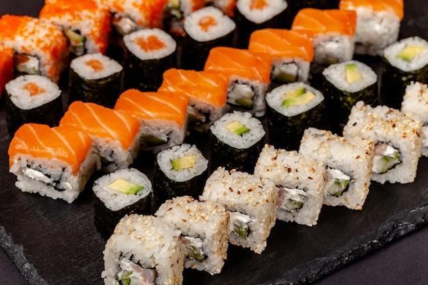 Set van sushi en broodjes liggen op een stenen schoolbord.