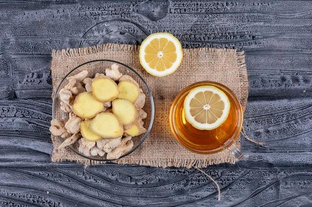 Set van thee, citroen en gember segmenten en gember op een zak doek en donkere houten achtergrond. plat lag.