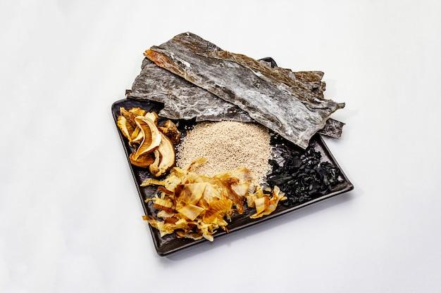 Set van traditionele japanse ingrediënt voor het koken van basis dashi bouillon. algen kombu en wakame, katsuobushi en droge champignons. geïsoleerd