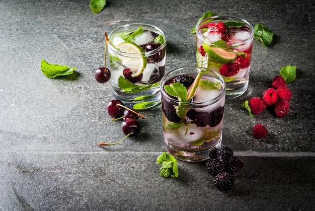 Set van traditionele zomer verfrissende drankjes berry mojito. met limoen, muntblaadjes, bramen, frambozen en kersen. met de ingrediënten op een donkere stenen tafel.