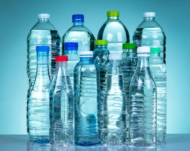 Set van transparante plastic fles water met blanco label. helder water en natuurlijke minerale fles met witte, groene, rode en blauwe dop. gezond drankje. collectie van plastic fles.