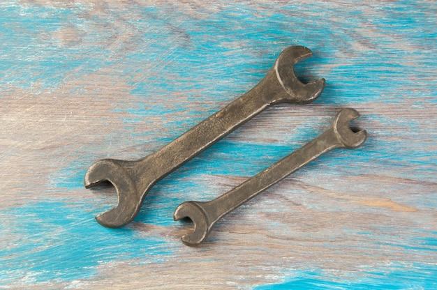 Set van twee vintage bronzen moersleutel op armoedige blauwe houten achtergrond. ruimte voor tekst kopiëren.