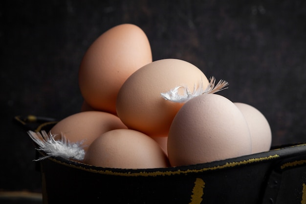 Set van veren en eieren in een pot op een donkere houten achtergrond. detailopname.