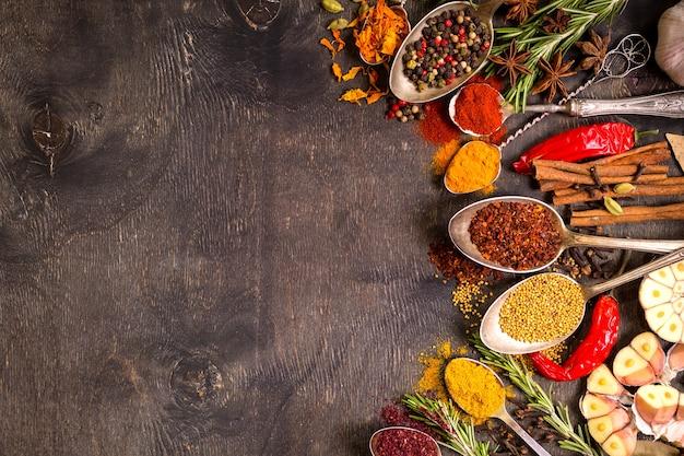 Set van verschillende aromatische kleurrijke kruiden in oude vintage lepels en kruiden op een donkere houten achtergrond.