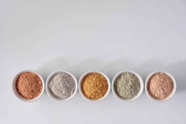 Set van verschillende cosmetische klei modderpoeders op witte ondergrond