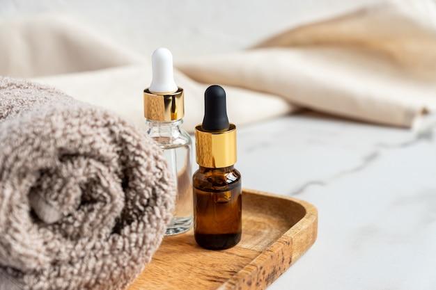 Set van verschillende flessen met schoonheidsserum, hyaluronzuur en vitamines op houten dienblad met handdoek.