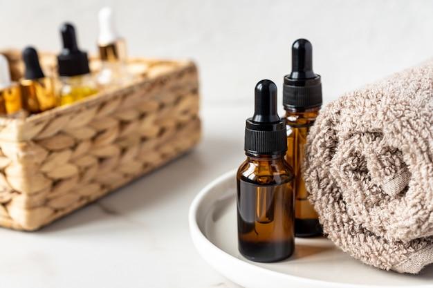 Set van verschillende flessen met serum, hyaluronzuur en vitamines op houten dienblad met handdoek.