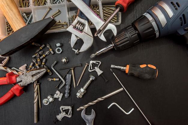 Set van verschillende gereedschappen met boren, schroeven, schroevendraaierbits en inbussleutel voor reparatie op bureau