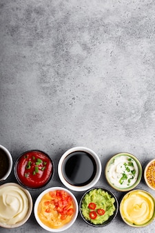 Set van verschillende gezonde sauzen in kommen op rustieke betonnen achtergrond, bovenaanzicht, close-up. ruimte voor tekst. tomatenketchup, mayonaise, guacamole, mosterd, pesto, kaassaus - assortiment dips