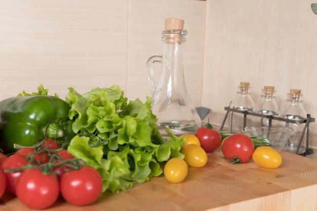 Set van verschillende groente op snijplank op keuken. gezonde eetconcepten. salade-ingrediënten, tomaten, paprika, olijfolie, kruiden