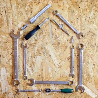 Set van verschillende handgereedschappen voor reparatie of automonteursgereedschap in de vorm van een huisvorm. reparatie tool kit. apparatuur voor de bouw. houten achtergrond, patroon, bovenaanzicht. vierkant