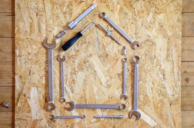Set van verschillende handgereedschappen voor reparatie of automonteursgereedschap in de vorm van een huisvorm. reparatie tool kit. apparatuur voor de bouw. houten achtergrond, patroon, bovenaanzicht