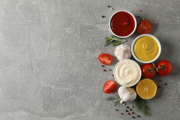 Set van verschillende heerlijke sauzen, knoflook, cherrytomaatjes, olijfolie op grijze achtergrond, bovenaanzicht. ruimte voor tekst