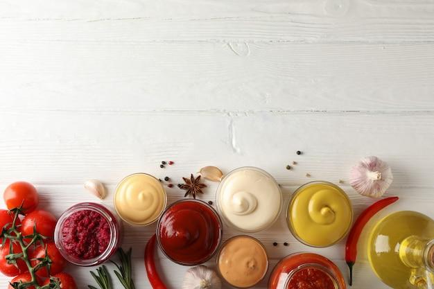 Set van verschillende heerlijke sauzen, knoflook, cherrytomaatjes, olijfolie op witte achtergrond, ruimte voor tekst. bovenaanzicht