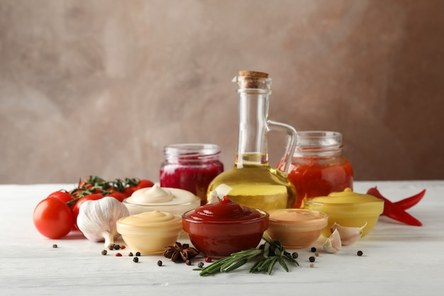 Set van verschillende heerlijke sauzen, knoflook, cherrytomaatjes, olijfolie op witte achtergrond, ruimte voor tekst