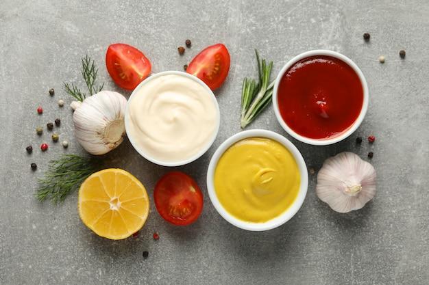 Set van verschillende heerlijke sauzen, knoflook, cherrytomaatjes op grijze achtergrond, ruimte voor tekst. bovenaanzicht