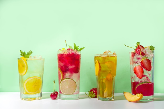 Set van verschillende koude zomercocktails - perzikthee, limonade, mojito, kersenmocktail, met fruit