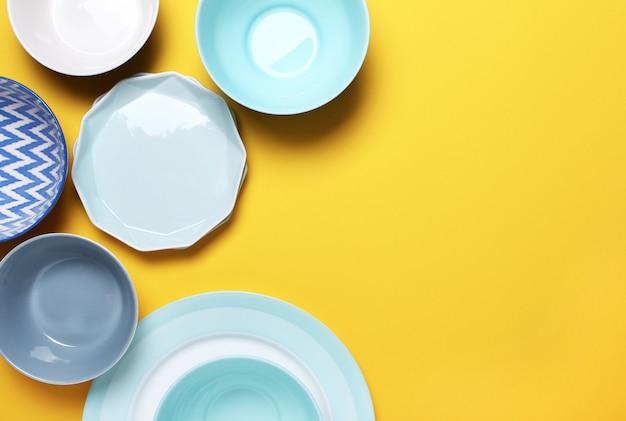 Set van verschillende moderne witte en blauwe borden en kommen op geel.