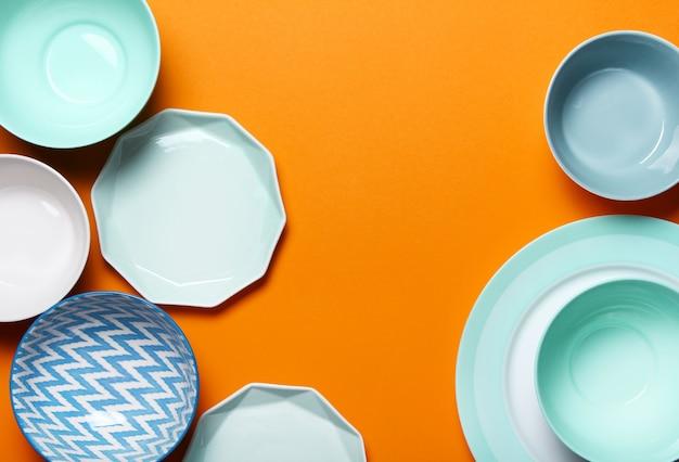 Set van verschillende moderne witte en blauwe borden en kommen op oranje