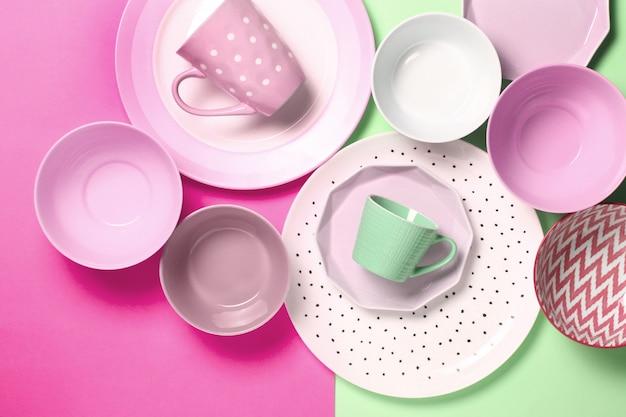Set van verschillende moderne witte en roze borden, kommen en kopjes op roze en groen.