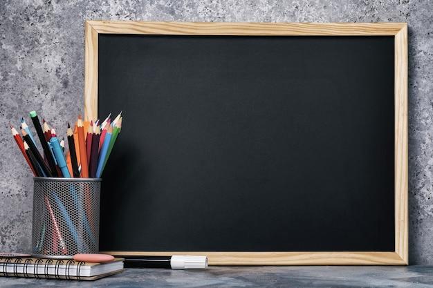 Set van verschillende potloden pennen en een krijtbord met kopie ruimte
