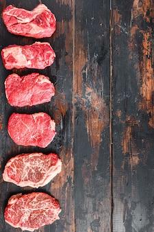 Set van verschillende rauwe biefstuk met kruiden op oude houten donkere planken bovenaanzicht.