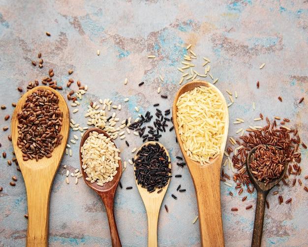 Set van verschillende rijst op betonnen tafel: zwarte, basmati, bruine en rode gemengde rijst