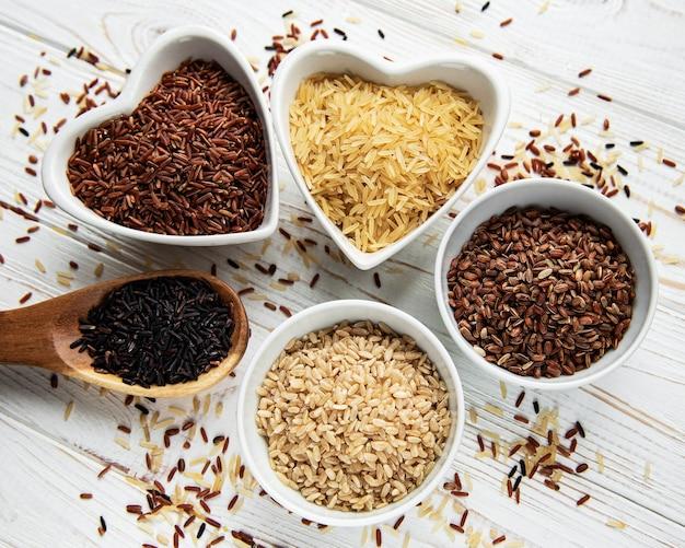 Set van verschillende rijst op witte houten achtergrond zwarte basmati bruine en rode gemengde rijst