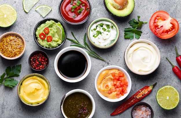 Set van verschillende sauzen in kommen en ingrediënten op grijze rustieke betonnen achtergrond, bovenaanzicht. tomatenketchup, mayonaise, guacamole, mosterd, sojasaus, pesto, kaassaus - assortiment dips