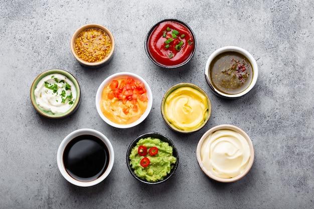 Set van verschillende sauzen in kommen op grijze rustieke betonnen achtergrond, bovenaanzicht, close-up. tomatenketchup, mayonaise, guacamole, mosterd, sojasaus, pesto, kaassaus - assortiment dips