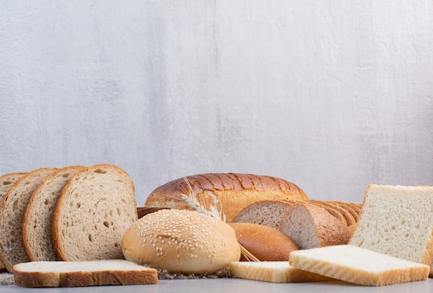 Set van verschillende sneetjes brood op marmeren oppervlak