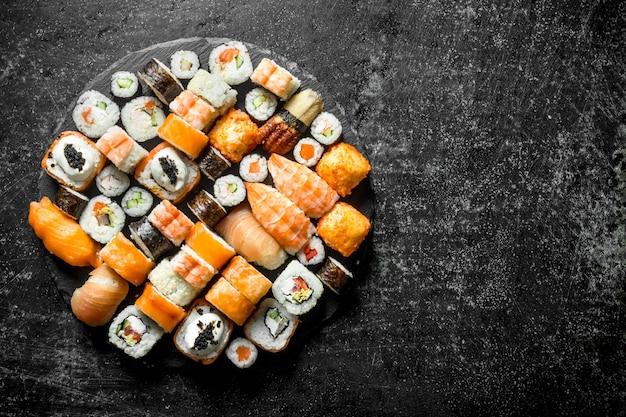 Set van verschillende soorten sushi rolt op een ronde stenen bord. op donkere rustieke tafel