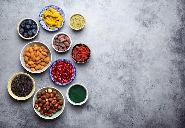 Set van verschillende superfoods in kommen op steengrijze achtergrond: spirulina, gojibes, cacao, matcha groene thee, quinoa, chiazaden, bosbessen, noten voor gelukkig gezond leven, bovenaanzicht, kopieer ruimte
