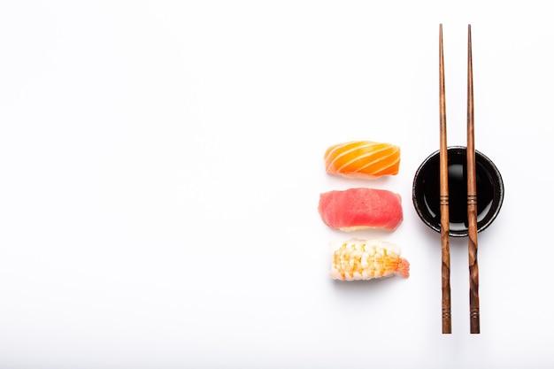 Set van verschillende sushi nigiri, sojasaus en eetstokjes op witte achtergrond met kopie ruimte, bovenaanzicht. traditioneel japans sushiconcept, close-up