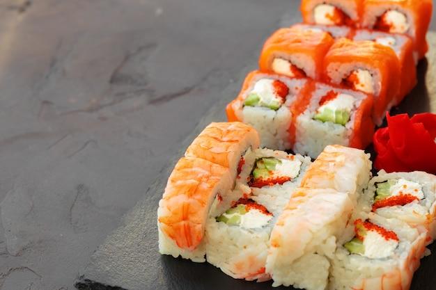 Set van verschillende sushibroodjes geserveerd op grijze tafel