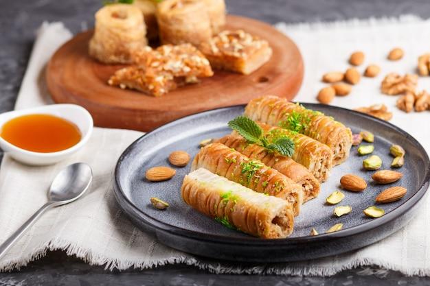 Set van verschillende traditionele arabische zoetigheden: baklava, kunafa, basbus in keramische platen op een grijs beton. zijaanzicht.