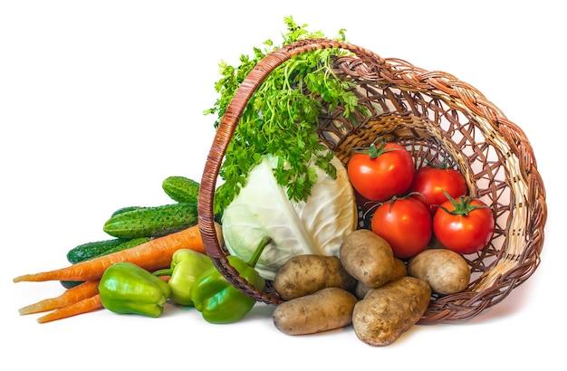 Set van verse groenten in een rieten mand geïsoleerd op een witte achtergrond