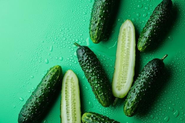 Set van verse hele en gesneden komkommers op een groene achtergrond met waterdruppels. tuin komkommer behang achtergrond ontwerp
