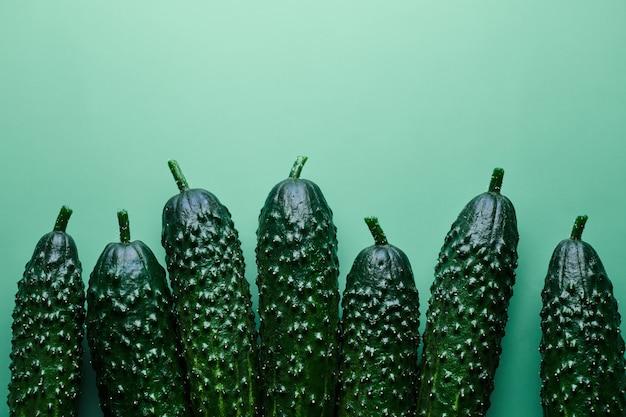 Set van verse hele komkommers op een groene achtergrond, voedselpatroon. tuin komkommer behang achtergrond ontwerp