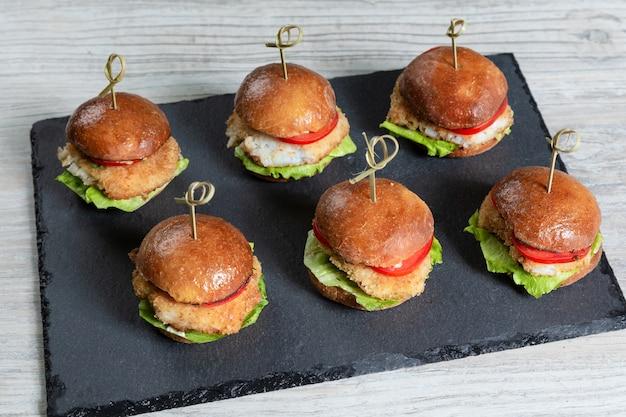 Set van vis hamburgers op zwarte bord op houten tafel