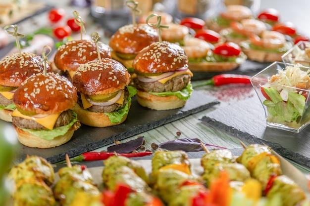 Set van vlees hamburgers op zwarte bord op houten tafel