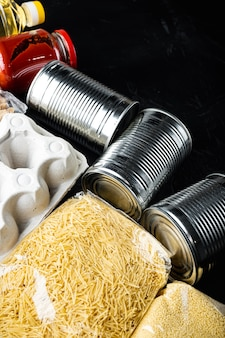 Set van voedingsproducten. voedselvoorraad. donatie, coronavirus en quarantaineconcept met kopieerruimte, op zwarte achtergrond