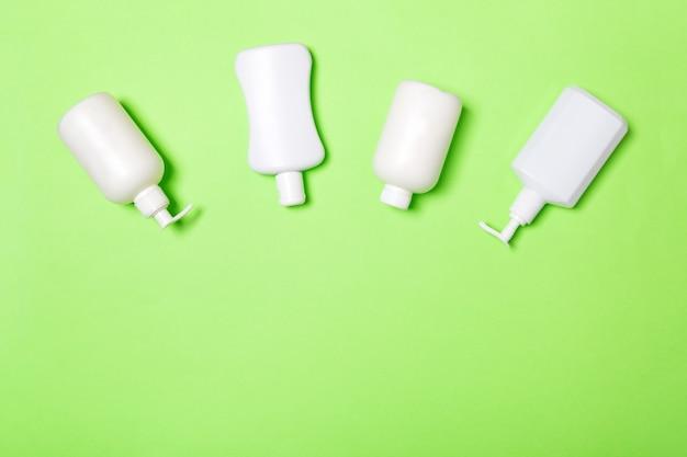 Set van witte cosmetische containers op groene achtergrond, bovenaanzicht met kopie ruimte. groep plastic flessen voor lichaamsverzorging