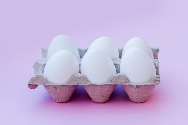 Set van witte eieren op een roze achtergrond