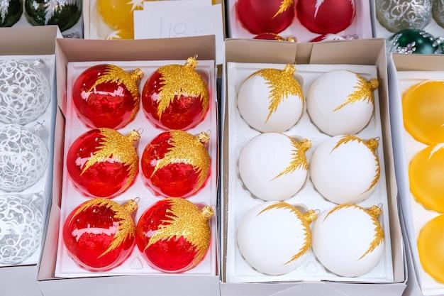 Set van witte en rode kerstballen in een doos. kerstversieringen worden op een markt verkocht.