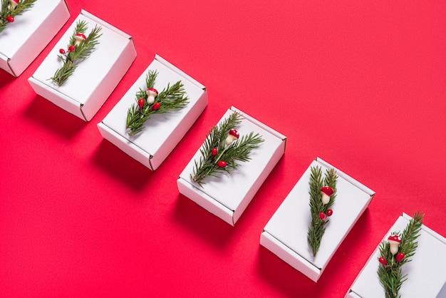 Set van witte kartonnen dozen versierd met kerstboom ornament op rood