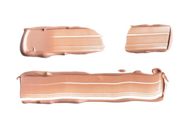 Set van zacht beige uitstrijkjes van make-up romige foundation geïsoleerd op een witte achtergrond. cosmetische camouflagestift. realistische bruine crèmetextuur voor make-up.
