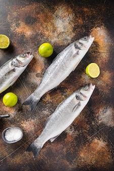 Set van zeebaars met kruiden en specerijen ingrediënten over darc rustieke achtergrond bovenaanzicht.