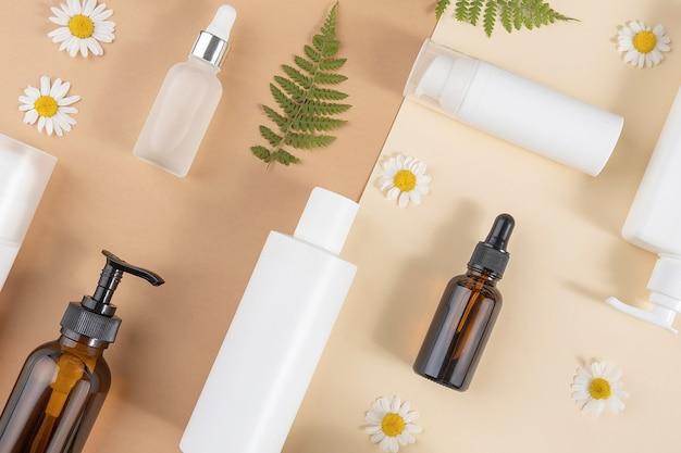 Set van zorg cosmetica. diverse flessen, buizen met cosmetica, kamille bloemen, varenbladeren op een beige en bruine achtergrond. schoonheidsconcept. bovenaanzicht plat lag.